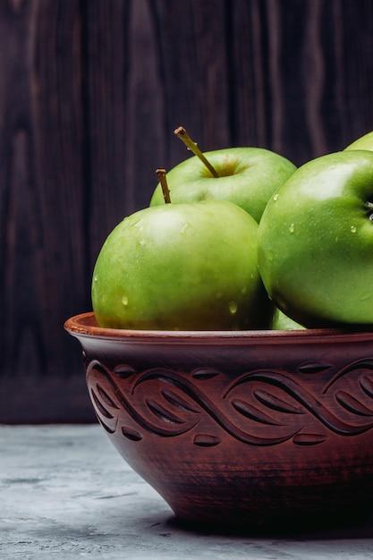 Reife grüne äpfel in einer schüssel auf einem dunklen hintergrund Premium Fotos