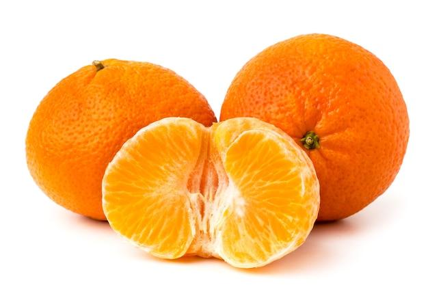 Reife mandarinen und die hälfte auf weiß, nahaufnahme. Premium Fotos