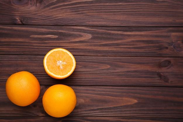 Reife orange frucht auf einem braunen hintergrund Premium Fotos