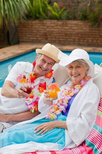 Reife paare, die ein cocktail neben dem swimmingpool trinken Premium Fotos