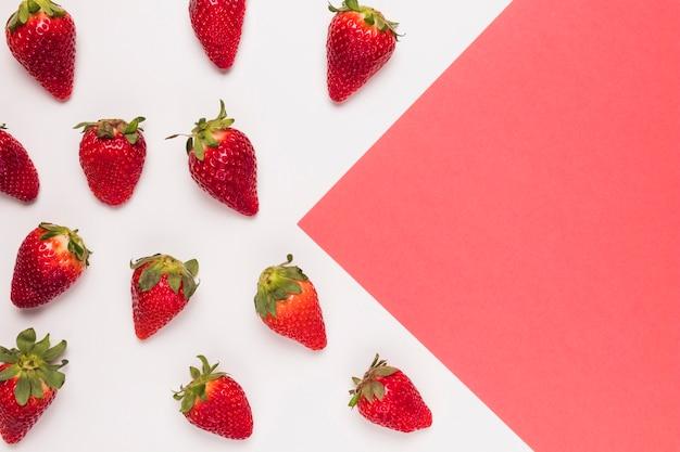 Reife rote erdbeeren auf rosafarbenem und weißem mehrfarbigem hintergrund Premium Fotos