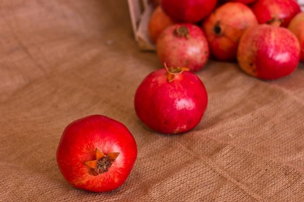 Reife rote granatäpfel auf brauner leinwand Premium Fotos