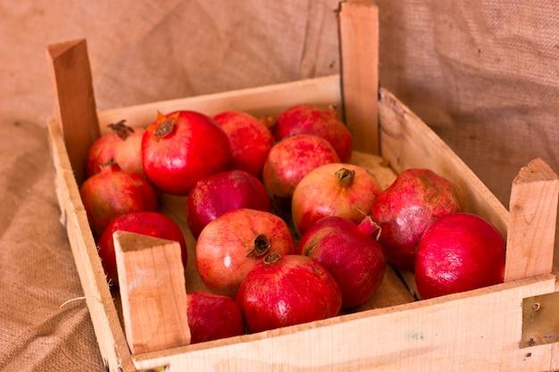 Reife rote granatäpfel in einer holzkiste auf brauner leinwand Premium Fotos