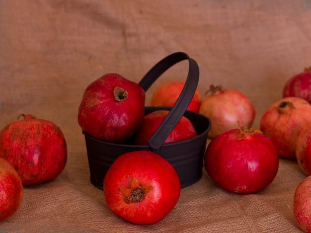 Reife rote granatäpfel in einer metallschwarzschüssel auf einer braunen leinwand Premium Fotos