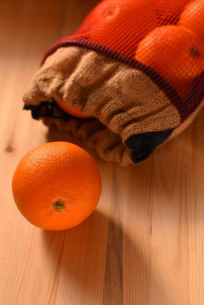 Reife saftige orange zerbröckelte aus einer segeltuchtasche auf einer holzoberfläche heraus Premium Fotos