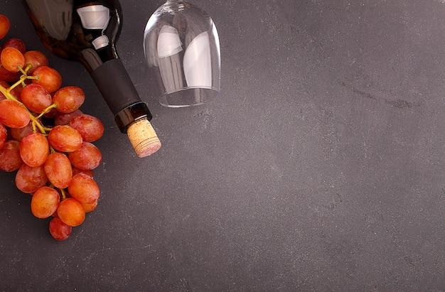 Reife trauben, rotwein und ein glas auf schwarzem hintergrund Premium Fotos