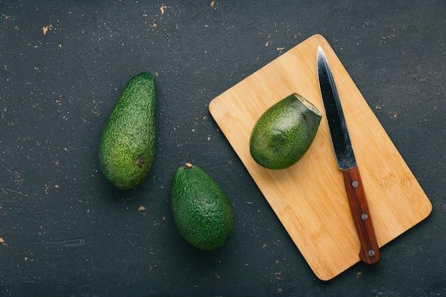 Reife und leckere avocado-früchte auf einem schneidebrett mit einem messer Premium Fotos