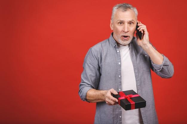 Reifer älterer mann, der ein geschenk mit rotem band als geschenk lokalisiert zeigt. telefon benutzen. Premium Fotos