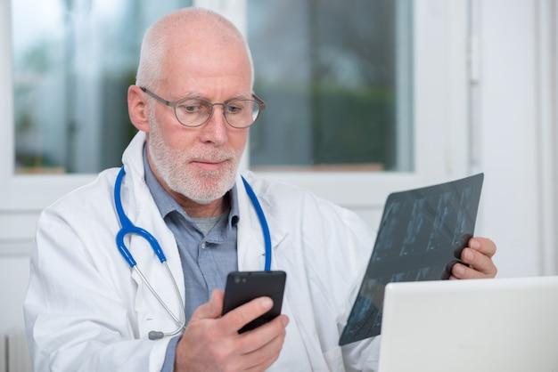 Reifer doktor, der röntgenstrahlbild betrachtet und telefon verwendet Premium Fotos