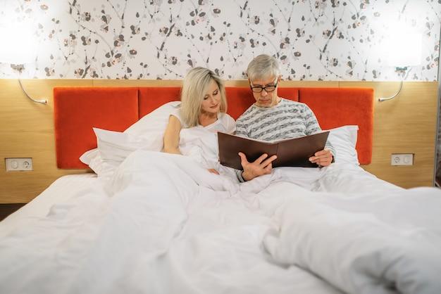 Reifer ehemann und ehefrau betrachten fotoalbum im schlafzimmer. mann und frau liegen im bett vor dem schlafengehen, glückliches liebespaar Premium Fotos