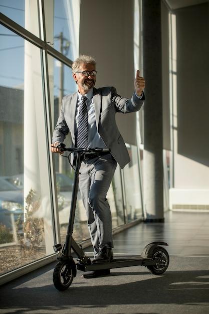 Reifer geschäftsmann, der mit elektroroller am bürofenster steht Premium Fotos