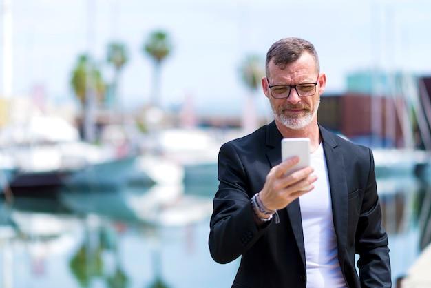 Reifer geschäftsmann unter verwendung des handys bei gegen hafen draußen stehen Premium Fotos