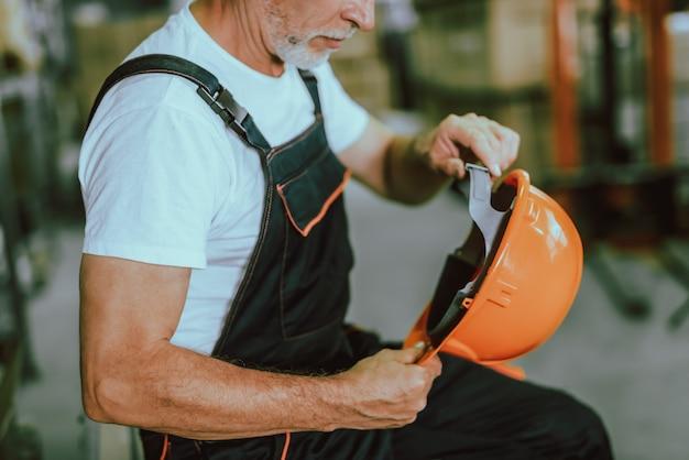 Reifer lagerarbeiter, der schutzhelm hält Premium Fotos