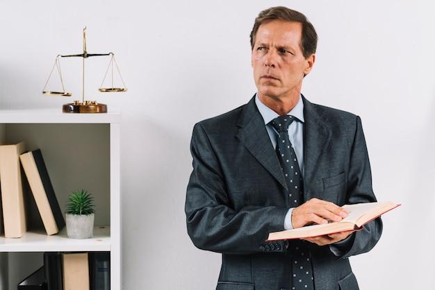 Reifer männlicher rechtsanwalt, der das gesetzesbuch steht im gerichtssaal hält Kostenlose Fotos