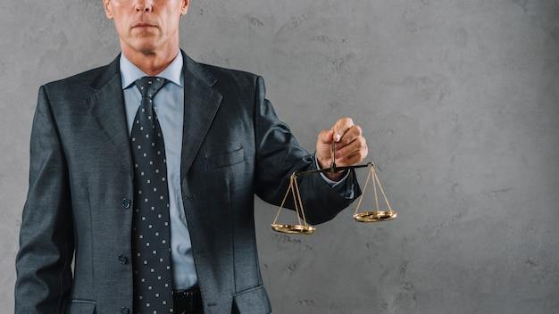 Reifer männlicher rechtsanwalt, der gerechtigkeitsskala gegen grauen strukturierten hintergrund hält Kostenlose Fotos