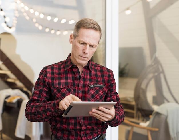 Reifer mann, der auf seiner tablette schaut Kostenlose Fotos