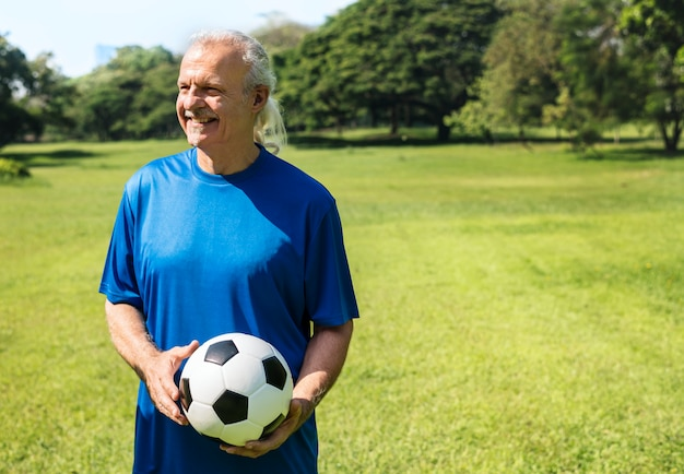Reifer mann, der einen fußball hält Kostenlose Fotos