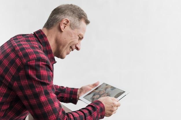 Reifer mann der seitenansicht, der auf fotos mit seinen kindern und enkelkindern schaut Kostenlose Fotos