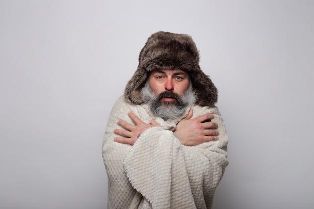 Reifer mann, der sich mit einer decke und einem hut bedeckt, die in der kälte zittern Premium Fotos