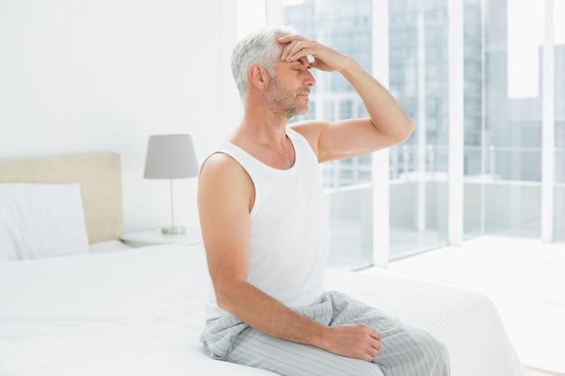 Reifer mann, der unter kopfschmerzen im bett leidet Premium Fotos