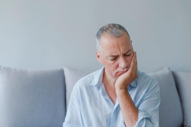 Reifer mann, der unter zahnschmerz, karies leidet Premium Fotos