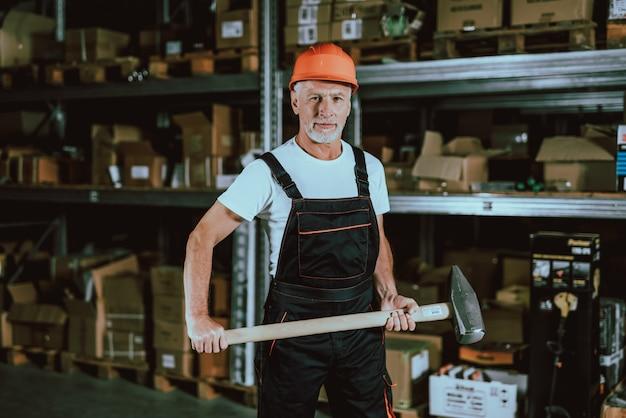 Reifer mann im schutzhelm mit vorschlaghammer Premium Fotos