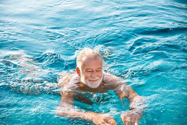 Reifer mann in einem swimmingpool Premium Fotos