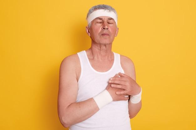 Reifer mann posiert mit geschlossenen augen und berührt seine brust, fühlt herzschmerzen, braucht behandlung, hat herzinfarkt nach dem sport Kostenlose Fotos