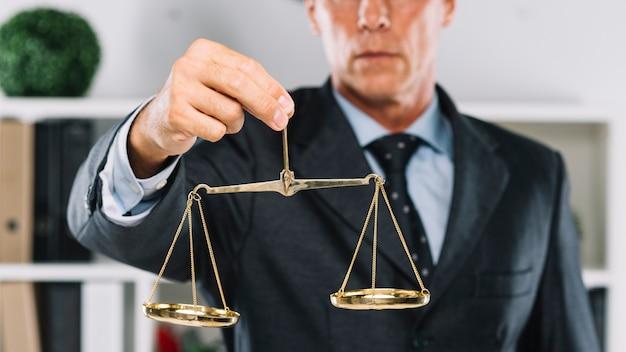 Reifer rechtsanwalt, der in der hand goldene skalen von gerechtigkeit hält Premium Fotos