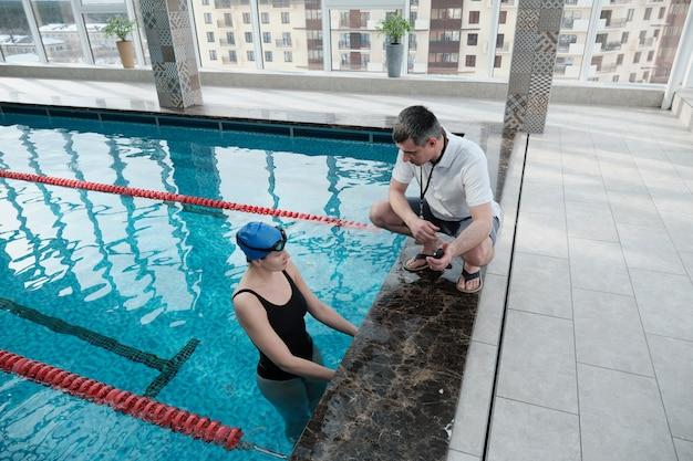 Reifer trainer mit pfeife am pool und ratschläge für schwimmer zur verbesserung der rundenzeit Premium Fotos
