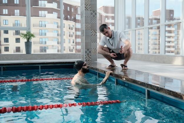 Reifer trainer mit pfeife, die dem schwimmer die rundenzeit auf der stoppuhr zeigt, während er den schwimmer auf den wettkampf vorbereitet Premium Fotos