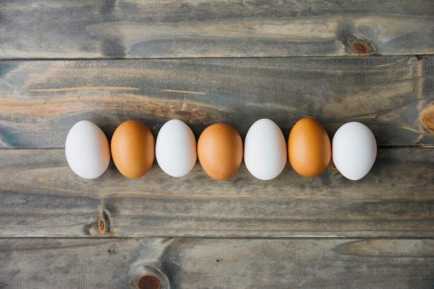 Reihe der braunen und weißen eier auf hölzerner planke Kostenlose Fotos