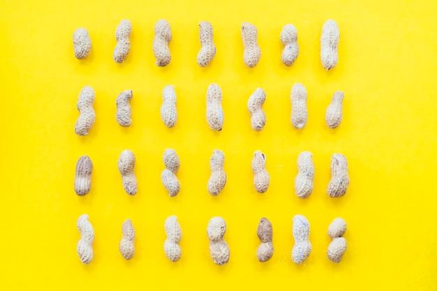 Reihe der erdnussshell auf gelbem hintergrund Kostenlose Fotos