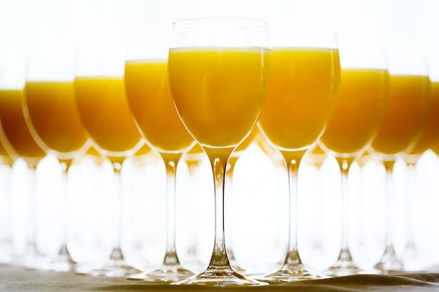 Reihe der gläser mit frischem orangensaft Premium Fotos