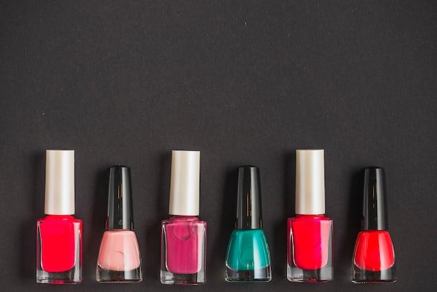 Reihe der multi farbigen nagellackflaschen auf schwarzem hintergrund Kostenlose Fotos