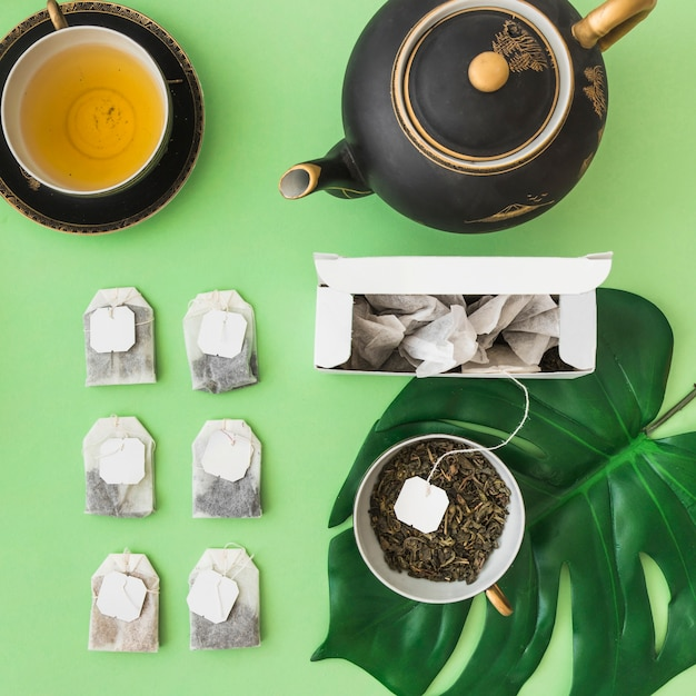 Reihe der verschiedenen teebeutel mit teeschale und teekanne auf blassem grünem hintergrund Kostenlose Fotos