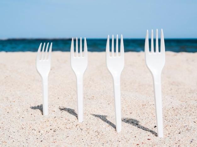Reihe der weißen plastikgabeln fest im sand auf strand Kostenlose Fotos