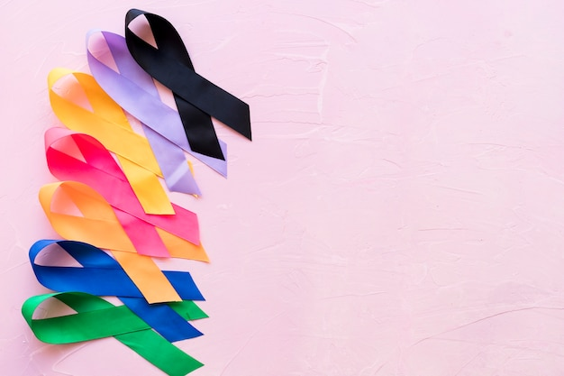 Reihe des hellen bunten bewusstseinsbandes auf rosa rauem hintergrund Kostenlose Fotos