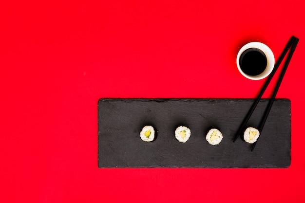 Reihe von asiatischen rollen auf schieferplatte mit essstäbchen und sojasoße über rotem hintergrund Kostenlose Fotos
