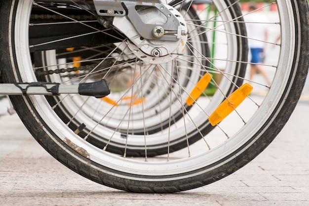 Reihe von geparkten weinlesefahrrädern fährt für miete auf bürgersteig rad. Premium Fotos