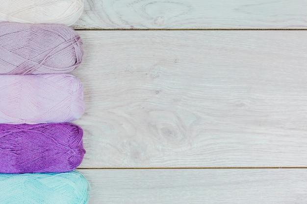 Reihe von lila; blaues und weißes strickgarn auf grauem hölzernem hintergrund Kostenlose Fotos