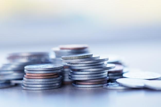 Reihe von münzen auf hölzernem hintergrund für finanz- und einsparungskonzept, investition, wirtschaft, weichzeichnung Premium Fotos