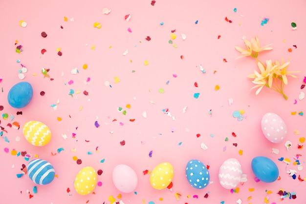 Reihe von ostereiern zwischen hellen konfetti Kostenlose Fotos