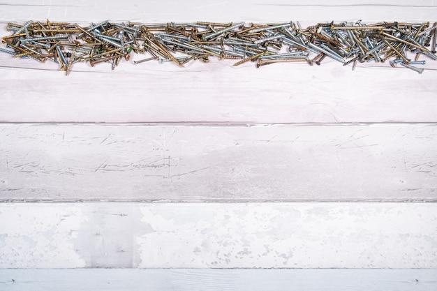 Reihe von schrauben verschiedener formen an der spitze eines freien raumes auf hölzernem hintergrund. draufsicht mit platz für text Premium Fotos