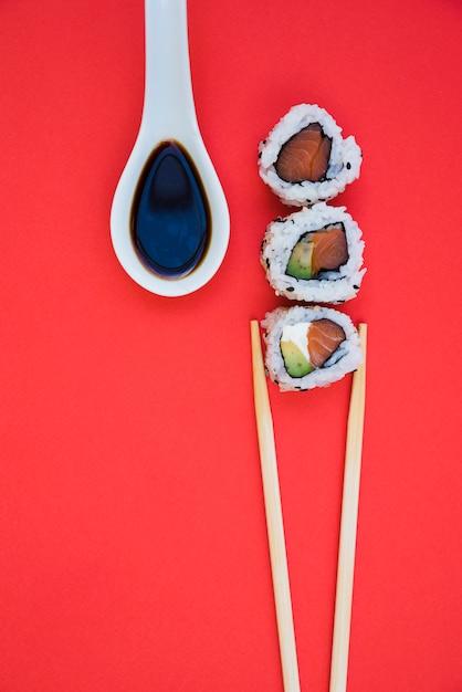 Reihe von sushirollen mit essstäbchen und sojasoße im weißen löffel über rotem hintergrund Kostenlose Fotos