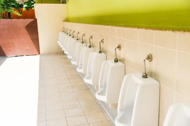 Reihe von toilettenblöcken der toilette für mann auf fliesenwand Premium Fotos