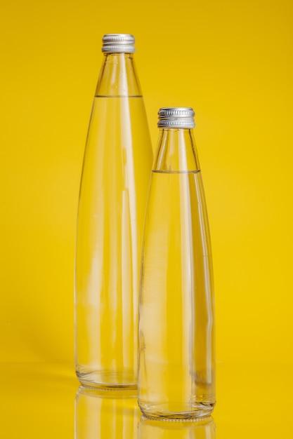 Reines wasser in der plastikflasche auf hellem gelbem hintergrund Premium Fotos