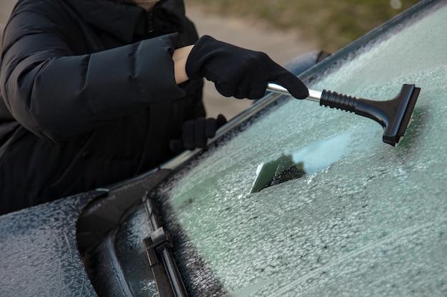 Reinigen sie das autofenster im winter vom schnee. reinigung von windschutzscheibenautos. eis und schnee von den fenstern entfernen. Premium Fotos