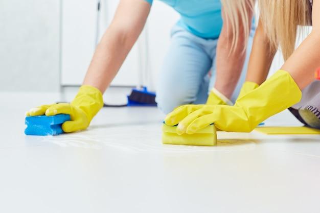 Reinigen, waschen. eine nahaufnahme von händen mit handschuhen beim reinigen des hauses. Premium Fotos