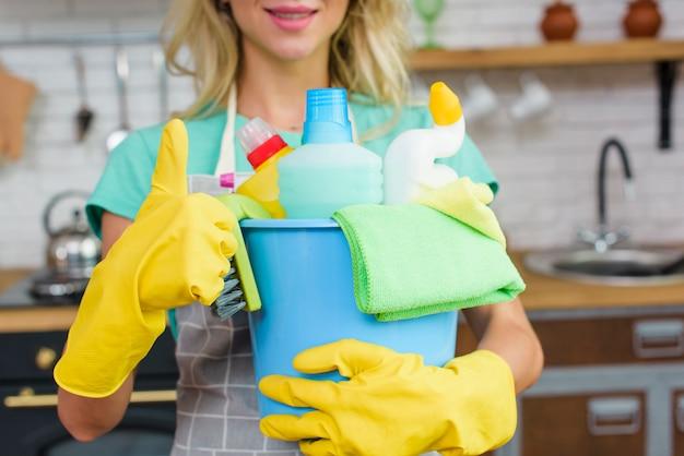 Reiniger, der die reinigungswerkzeuge und -produkte zeigen daumengeste hält Kostenlose Fotos
